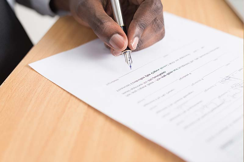 Man signing contract for a buy-to-let mortgage in Germany.