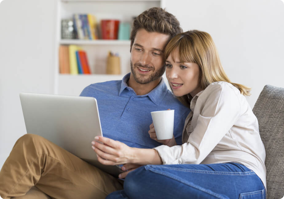 Young couple sitting on a sofa while looking for property to buy in Germany through browsing online websites in their laptop.